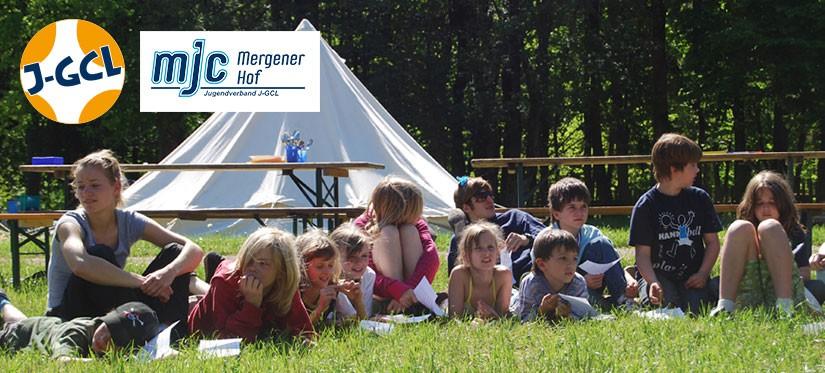 Kinder auf Wiese mit Zelt im Hintergrund